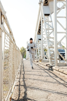 Full length portrait of a concentrated young sports man jogging across bridge outdoors