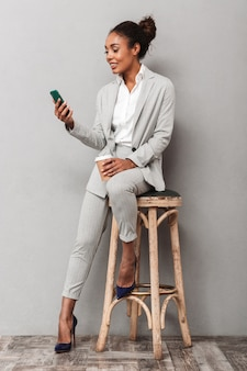 Full length portrait of a confident african business woman wearing suit sitting on a chair, holding takeaway coffee, using mobile phone
