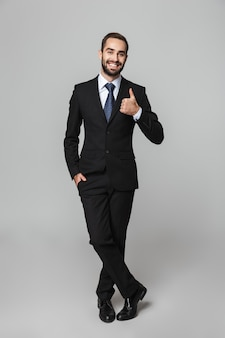 Full length portrait of a confident handsome businessman wearing suit isolated
