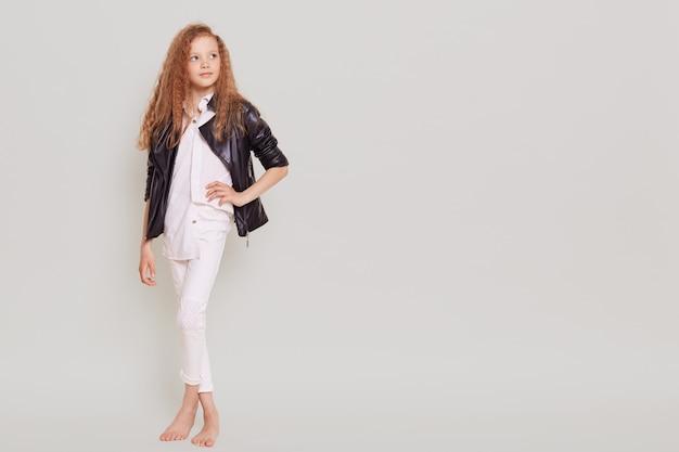 Ritratto integrale della piccola scolara sicura che indossa vestiti bianchi e giacca di pelle che distoglie lo sguardo e tiene la mano sull'anca