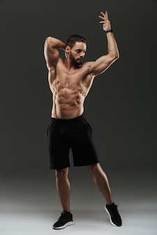 Full length portrait of a confident muscular man posing