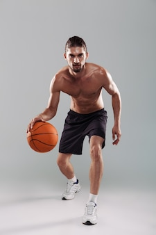 Full length portrait of a confident young shirtless man