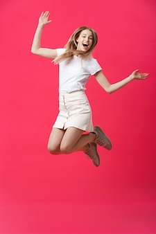 Full length portrait of a crazy joyful girl in casual cloth while jumping isolated over pink background