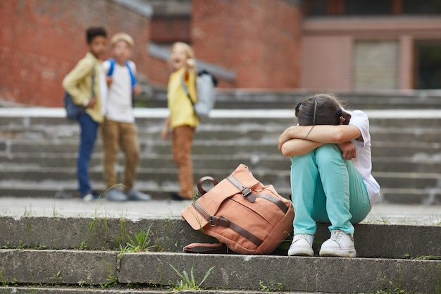 Full length portrait of crying schoolgirl sitting on stairs outdoors with group of teasing children bullying her in background, copy space