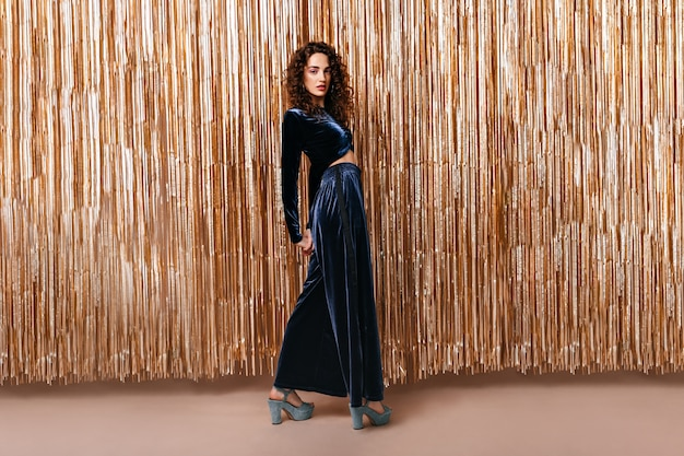Full length portrait of curly lady dressed in velvet suit on gold background