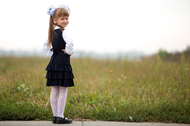 Full-length portrait of cute adorable serious thoughtful first grader girl in school uniform and white bows in long blond hair on blurred light green sunny grass and white sky background