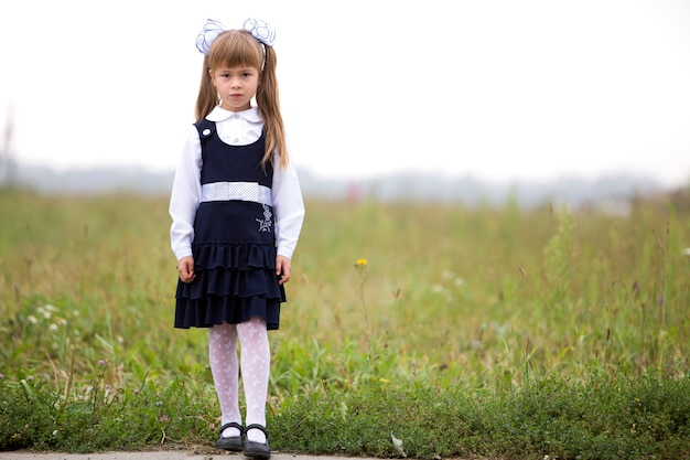 Full-length portrait of cute adorable serious thoughtful first grader girl in school uniform and white bows in long blond hair on blurred light green sunny grass