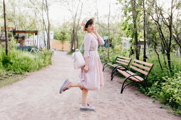 Full-length portrait of cute dark-haired lady, posing in the middle of park alley in morning
