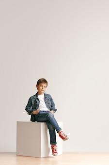 Ritratto integrale del ragazzino sveglio in vestiti di jeans alla moda e sorridente, in piedi sul bianco. concetto di moda per bambini