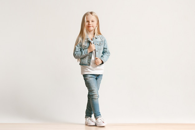 Full length portrait of cute little kid girl in stylish jeans clothes and smiling, standing on white. kids fashion concept