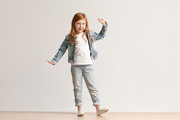 Full length portrait of cute little kid in stylish jeans clothes smiling