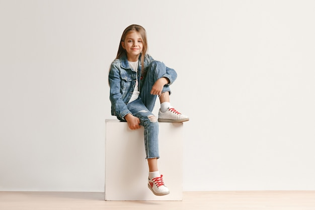 Full length portrait of cute little teen in stylish jeans clothes looking at camera and smiling