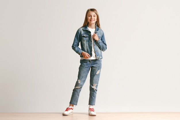 Full length portrait of cute little teen in stylish jeans clothes smiling