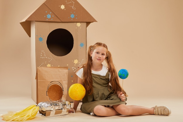 Full length portrait of cute red haired girl playing astronaut while sitting on floor on cardboard rocket