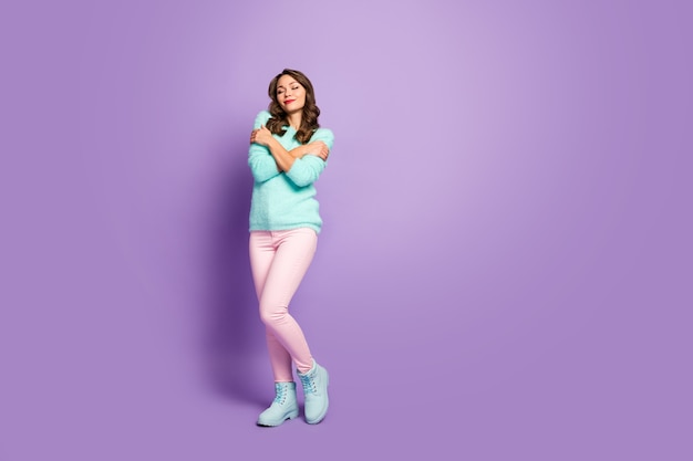 Full length portrait of cute sweet positive girl have turquoise warm woolen pullover hug herself enjoy close eyes wear good look outfit.