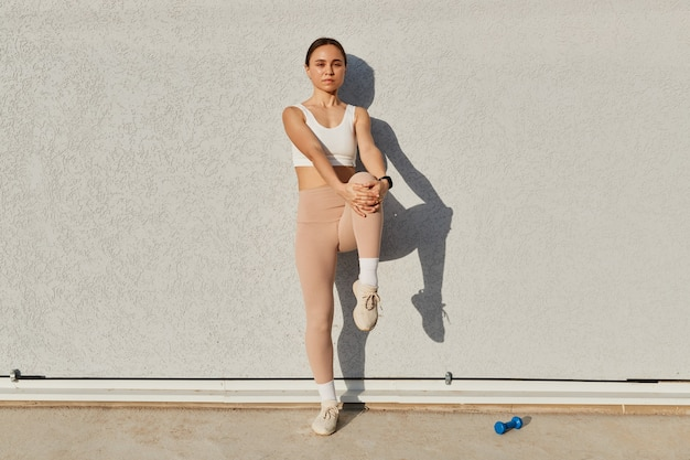Full length portrait of dark haired female wearing white sporty top and beige leggins looking at camera with serious expression, standing stretching leg before workout, healthy lifestyle.