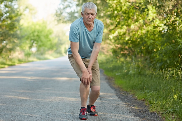 Full length portrait of displeased male pensioner, leans on knees, has pain after jogging, banged his leg, stands on road in rural area