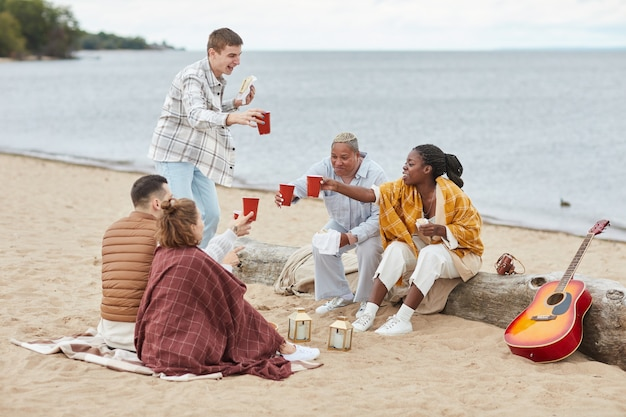 Full length portrait of diverse group of friends clinking beer cups on beach in autumn and laughing