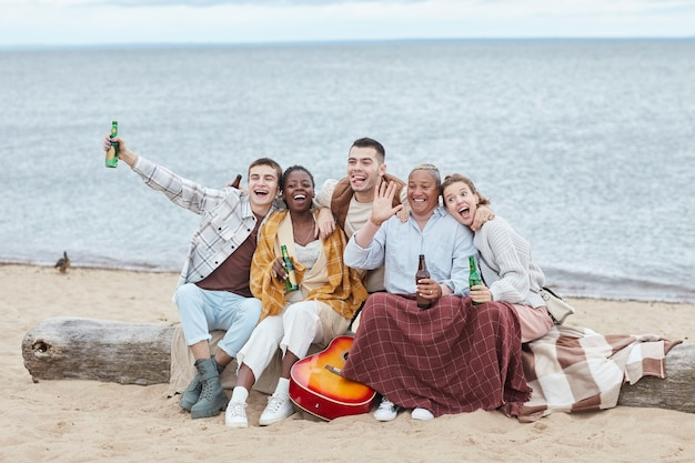 Full length portrait of diverse group of friends enjoying camping on beach in autumn and posing for photo