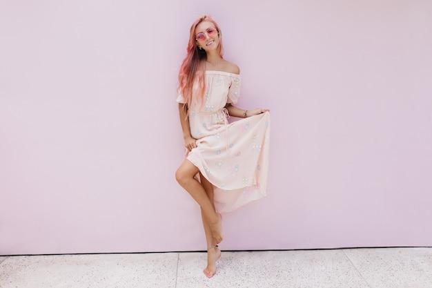 Ritratto integrale della ragazza elegante che gioca con il vestito lungo