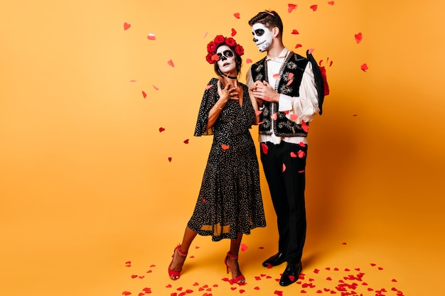 Ritratto a figura intera della ragazza elegante zombie latina in posa a halloween con il fidanzato.