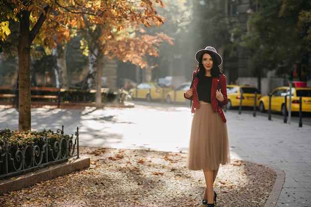 Full-length portrait of enchanting brunette woman standing on the street in sunny day