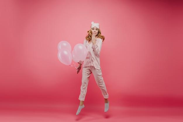 Ritratto integrale di donna entusiasta in pigiama che salta con palloncini al mattino. felice ragazza di compleanno con i capelli ricci che scherza sul muro rosa brillante.