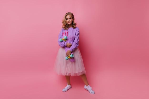 Ritratto integrale di giovane donna entusiasta indossa una gonna bianca lussureggiante. ragazza romantica con lo skateboard in piedi su roseo.