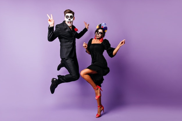 Full-length portrait of european couple dancing on purple background in zombie costumes. funny young people fooling around at halloween event.