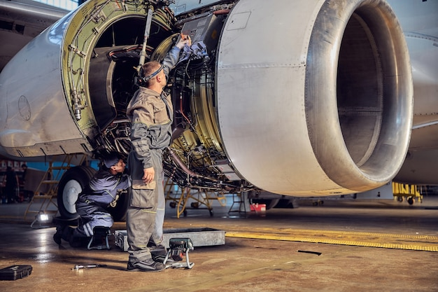 Full length portrait of european man engineer and technician are repairing aircraft in the aviation hangar