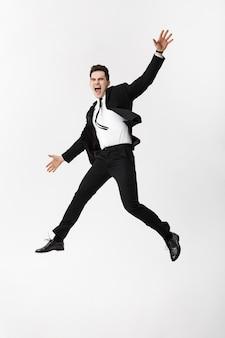 フルレングスのポートレート興奮したビジネスマンのお祝いの成功。白と灰色の背景に分離