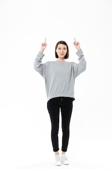 Full length portrait of an excited casual woman pointing