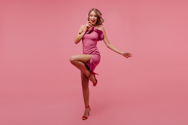 Full-length portrait of excited curly woman standing on one leg on pink wall