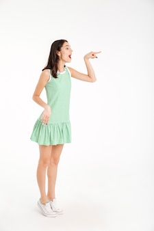 Full length portrait of an excited girl dressed in dress