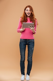 Full length portrait of an excited pretty redhead girl holding tablet