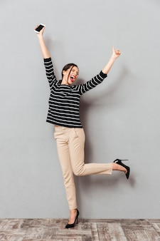 Full length portrait of an excited woman