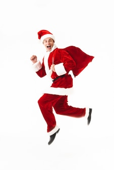 Full length portrait of an excited young man dressed in santa claus costume jumping isolated over white space