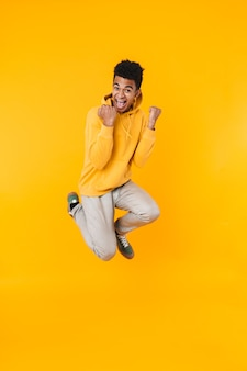 Full length portrait of an excited young teenager boy jumping isolated over yellow wall, celebrating