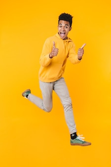 Full length portrait of an excited young teenager boy jumping isolated over yellow wall, showing thumbs up