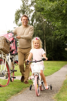 Full length portrait of father and daughter cycling together in park