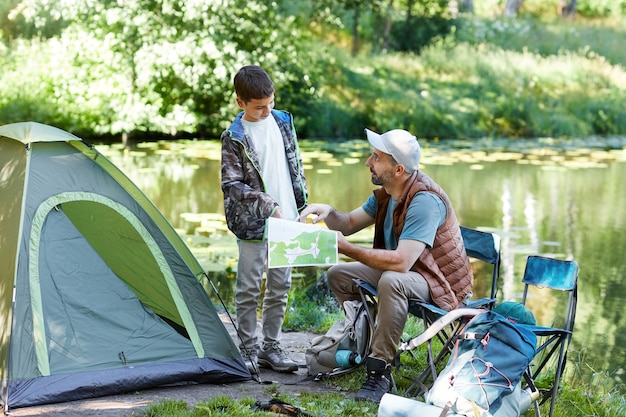 Full length portrait of father and son looking at map while enjoying camping trip together by lake, copy space