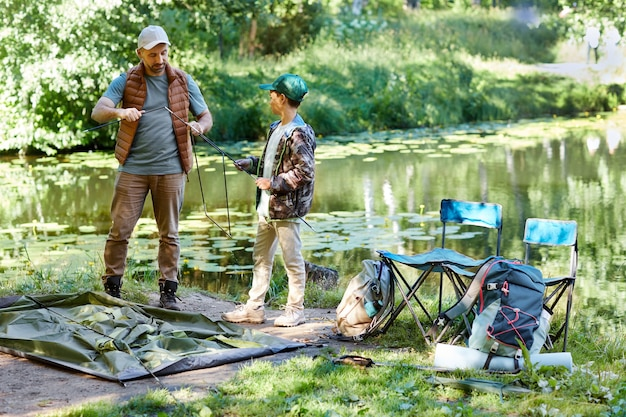 Full length portrait of father and son setting up tent together while camping by lake in nature, copy space