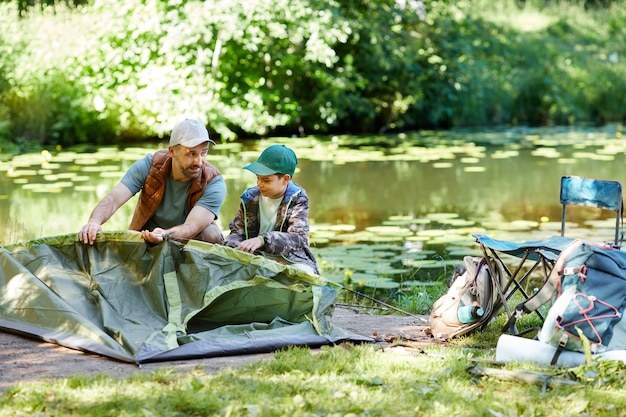 Full length portrait of father and son setting up tent together while enjoying camping by lake in forest, copy space