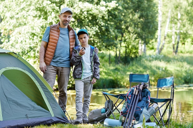 Full length portrait of father and son  while standing by tent and enjoying camping trip, copy space