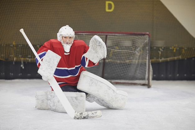 Full length portrait of female hockey player in full gear