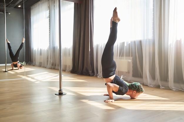 Full length portrait of female pole dancer doing hard acrobatic element while raising legs in dance class