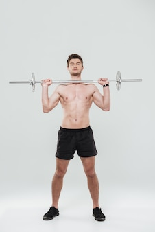 Full length portrait of a fit sportsman lifting heavy barbell