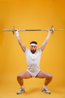 Full length portrait of a fitness man squatting with barbell