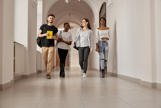 Full length portrait of four mixed-race group of young smiling people,casual dressed, walking through the bright university corridor. happy attractive students are going home after finishing lessons.