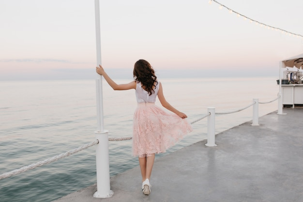 Портрет в полный рост элегантной брюнетки, идущей вдоль набережной океана и наслаждающейся прекрасным утренним видом